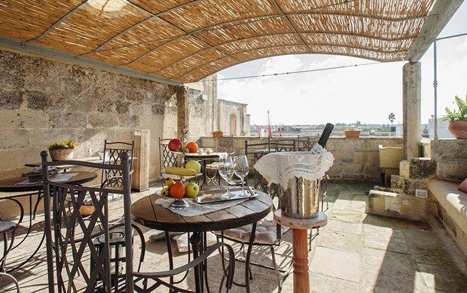 Overdekt buitenterras met stoelen en tafels van hotel Borgoterra fly & drive Puglia