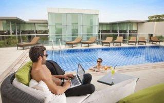 Dakterras met zonneterras en zwembad van Hotel Centro Basrha in Dubai
