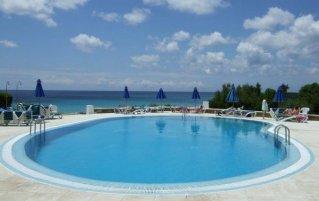 Zwembad en uitzicht op zee bij Aparthotel Vistamar op Menorca